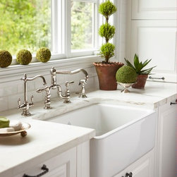 Functional Sophistication - A beautifully integrated farmhouse sink is surrounded by immaculate white marble and flanked by integrated Dishwasher.