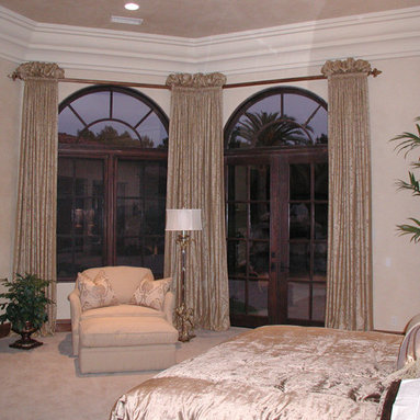 Custom Draperies - Ruched top silk draperies gathered onto a large iron pole mounted below the crown molding to frame the large arched top doors and window.