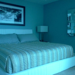 Blinds, shades and shutters - We were asked to create a bedspread and pillow shams to blend the cool blue and grey tones of this room.  We used the same fabric from the bed as a welt on the shams.