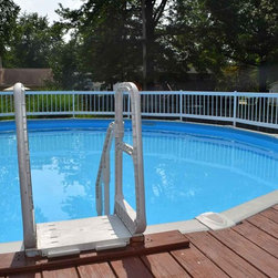 Above ground with fence around edge of pool - This beautiful above ground pool features a fence around the edge of the pool as well as a deck attached to the pool for poolside relaxation.
