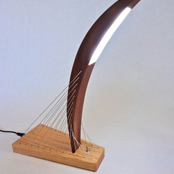 Signature Lamp - A modern lamp made of a mahogany curve perched atop a red oak base, the Signature Lamp is also an intriguing sculptural piece. The central curve is not attached to the base by any kind of fastener or adhesive, but is instead held firmly in place by the counteracting forces provided by the cables that pass through it. The LEDs, though small, are very bright and allow the lamp to function well as a desktop task lamp.