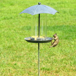 """Cat and Glass Bird Feeder - Apparently this feline failed to calculate this approximate squat and leap required to reach this raised feeder. Umbrella top protects seed from moisture; mostly aluminum construction; feed canister itself is glass. Dimensions: 16.5""""w x 14""""d x 49""""h"""