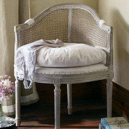 Delphine Chair - A curved feminine shape, caned back and carved Louis XVI frame gives Delphine elegant presence; the slouchy down-wrapped cushion, bartack trim and chalky gray finish enhance its elegant appeal. Crafted of solid oak, with lovely petite proportions