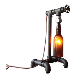 Peared Creation - Brewmaster Lamp, Amber Bottle - This lamp is constructed from industrial style black iron piping. The vintage bottle is firmly secured by custom rubber gaskets that grasp the bottle without causing damage. A low wattage bulb is used to illuminate the vintage amber bottle producing a warm ambient light. A rotating faucet handle serves as a switch to turn the light on and off, a new feature we are excited about! Power is supplied by a retro style cloth covered lamp cord and plug.