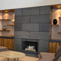 Ratcliffe penthouse - Custom concrete fireplace flanked by walnut cabinetry and concrete countertops.