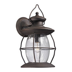 Elk Lighting - EL-47044/1 Village Lantern 1-Light Outdoor Sconce in Weathered Charcoal - Historic charm is captured in the Village Lantern Collection. This series has a clear glass fount inside a weathered charcoal finished wire frame. The handle that adorns the top of the fixture captures the authenticity reiminsant of the function these type of lights had years ago.