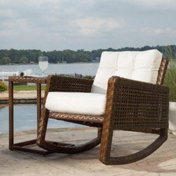 "Panama Jack St. Barths Rocking Chair with Cushion - Brown Pine with Viro Fiber - Rock the day away in the comfort of the Panama Jack St. Barths Rocking Chair with Cushion - Brown Pine with Viro Wicker. Ideal for any outdoor furniture setting, the rocking chair is built from an extruded aluminum frame with an exclusive thick woven Viro wicker fiber. Fast-drying cushions with outdoor fabric are durable for use all year round. The wicker is both weather- and UV-resistant for durable outdoor use, and the aluminum will never rust. Dimensions: 30W x 39D x 26H inches.About Hospitality RattanHospitality Rattan has been a leading manufacturer and distributor of contract quality rattan, wicker, and bamboo furnishings since 2000. The company's product lines have become dominant in the Casual Rattan, Wicker, and Outdoor Markets because of their quality construction, variety, and attractive design. Designed for buyers who appreciate upscale furniture with a tropical feel, Hospitality Rattan offers a range of indoor and outdoor collections featuring all-aluminum frames woven with Viro or Rehau synthetic wicker fiber that will not fade or crack when subjected to the elements. Hospitality Rattan furniture is manufactured to hospitality specifications and quality standards, which exceed the standards for residential use.Hospitality Rattan's Environmental CommitmentHospitality Rattan is continually looking for ways to limit their impact on the environment and is always trying to use the most environmentally friendly manufacturing techniques and materials possible. The company manufactures the highest quality furniture following sound and responsible environmental policies, with minimal impact on natural resources. Hospitality Rattan is also committed to achieving environmental best practices throughout its activity whenever this is practical and takes responsibility for the development and implementation of environmental best practices throughout all operations. Hospitality Rattan maintains a policy of continuous environmental improvement and therefore is a continuing work in progress.Hospitality Rattan's Environmentally Friendly Manufacturing ProcessAll of Hospitality Rattan products are green. From its basic raw materials of rattan poles, peels, leather, bamboo, abaca, lampacanay, wood, leather strips, and boards, down to other materials like nails, staples, water-based adhesives, finishes, stains, glazes and packing materials, all have minimum impact to the environment and are safe, biodegradable, recycled, and mostly recyclable. Aside from this, the products have undergone an environmentally-friendly process that makes them """"greener."""" The company's rattan components are sourced from sustained-yield managed forests, which means the methods used to grow and harvest the rattan vines ensure the long-term life of the forest and protect the biodiversity of the forest's ecosystems.Hospitality Rattan is committed to buying and using all materials, from rattan and hardwood to finishing materials, from reputable and renewable suppliers and seeks appropriate evidence that suppliers are in compliance with this policy. Hospitality Rattan strives to use materials that are processed in an environmentally responsible manner, or consist of a high level of recycled material. Finishing materials and stains used in Hospitality Rattan's furniture products consist of 75% water-based solutions which evaporate upon application with reduced or Volatile Organic Compounds (VOCs). The furniture factories use water-based glues, stains, topcoats and other finishes on all of their products. The switch from traditional solvent-based processes to water-based processes involved consolidating several processes by the factories, resulting in an 85% reduction in VOC emissions."