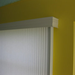 Vertical Cellular Shades in Lanai - This photo shows a close up of the faux wood valance across the top of the vertical cellular shade. The valance comes with the shade. This being an outside mount, the installer did a great job putting on a return (side piece).