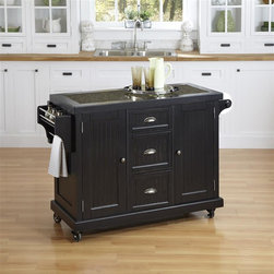 HomeStyles - Distressed Black Kitchen Cart - Give your home a cozy, inviting atmosphere with the Nantucket Kitchen Cart. It's sanded worn edges and distressed black finish provides the casual elegance that's great for any home decor style. The Nantucket Kitchen Cart is constructed of hardwood solids and engineered wood. Finishing process includes paint specking on the sanded and distressed finish providing a weathered look. Features include ���_ inch speckled multi-color black granite inset, two cabinet doors each containing an adjustable shelf, three storage shelves, built-in spice rack and towel bar, paper towel holder, and industrial size casters (two locking). 53.5 in. W x 20.75 in. D x 36.25 in. H