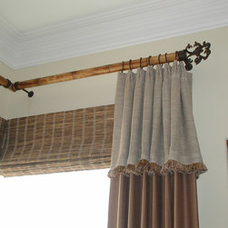 Custom Draperies - This photo shows a stationary side panel with top tacked pleats and attached cuff with brush fringe installed over butt and pass outside mounted woven wood shades. The draperies are installed on real bamboo poles with wrought iron rings, brackets and finials. Hardware is from Orion Ornamental Iron.