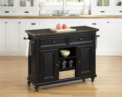 HomeStyles - Black Kitchen Cart - Inspired by the fusion of British colonial and old world tropical design, the Bermuda Kitchen Cart highlights poplar solids and engineered wood in a sleek, black finish. Further inspiration cab be found in the shutter style designed doors and intricate details. Bounteous storage is provided with two cabinet doors with one adjustable shelf behind each door, three adjustable shelves in middle, and two storage drawers. Other features include 7mm thick uniquely antiqued stainless steel top to complement the matching hardware, two towel bars, and industrial sized casters (two locking). This piece is finished with antique brass hardware. 44.5 in. W x 17.75 in. D x 32 in. H