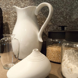 Adrienne DeRosa Photography © 2013 Houzz - White pottery punctuates the otherwise low-key setting near the range top, proving that form and function may indeed go hand-in-hand.  Whether used for their intended purposes or given a new task, pieces like these offer a refreshing presence in the kitchen.