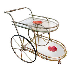 "Consigned Hollywood Regency Bar Cart - A stylish Hollywood Regency bar cart featuring oversized wheels, curvaceous lines with a glass top and bottom serving trays. Store and serve your liquor in style or use it for tea and coffee. This is a unique accent piece with a brass toned metal frame. Cheers!  18"" x 32"" x 30"" tall."
