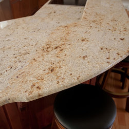 Antique White Grantie - A gentle granite with gold and amber mineral deposits on a white, cream, and grey background. Antique White Granite is quarried in India.