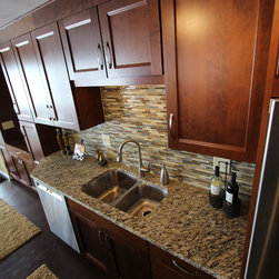 Kitchen Renovation, Lakewood, Ohio #1 ~ Waypoint Cabinetry - In this kitchen renovation we opened up the wall that separated the kitchen and living room to instantly create a feeling of a larger kitchen and allows for better interaction with guests.  Incorporating a breakfast bar added extra seating, a place to sit and converse with the cook while preparing meals and a place to set up a buffet when needed by utilizing the added counter surface.  The kitchen extended into the dining space by adding a base cabinet with wood top, flanked by two pantry cabinets. The products used are Waypoint Cherry Spice 420S Full Overlay Square Door Style with veneer flat panel accented with brushed nickel pulls.  Santa Cecilia granite countertops with an undermount stainless steel 60/40 sink and Moen Arbor High Arc faucet.  For the backsplash Bliss Amber Tea Linear Glass/Stone Blend tile was installed.  Accented with a Seagull custom design Ambiance low voltage rail system with 2 pendant lights and 8 directional spot lights.