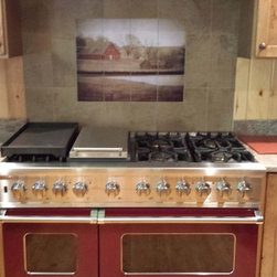 Vintage Farm Photo for Kitchen Backsplash Tile Idea - This kitchen remodel incorporates a vintage photo of a barn for kitchen backsplash tiles.  The photo adds a nice focal point while creating a stunning contrast to the Viking red kitchen range.