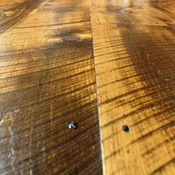 Hull Forest Products - Circular Sawn Wide Plank Pine Floors - Eastern White Pine flooring mill-direct from Hull Forest Products. Photo shows circle sawn solid wide pine plank floor with Walnut Old Masters stain and Waterlox satin tung oil finish. Floor planks shown are 7-11 inches wide.  (Widths from 5-23 inches are available.) This is newly sawn premium grade Eastern White Pine that has been skip planed and given circular saw marks for an antique look. The floor also features reproduction nails. Our wide pine is carefully selected from logs predominantly twelve feet and longer in order to ensure even growth and live red knots.  These logs come from second and third growth pine trees grown in historic and protected Connecticut forests, and the logs are harvested during the cold winter months for the best color retention.  Only sound red knots and very occasional small sound black knots or inclusions are allowed in this grade.