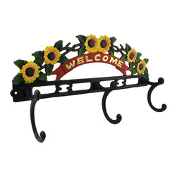 Painted Cast Iron `Welcome` Wall Plaque with 3 Hooks - This cheerful plaque features an arc of sunflowers with a `Welcome` banner below them and has 3 hat and coat hooks. It is a lovely addition to entryways in your home or office. Made of cast iron, this plaque measures 16 inches long, 8 inches tall, and 3 1/4 inches deep, including the hooks. This piece makes a lovely housewarming gift, and is sure to be admired wherever it is displayed.
