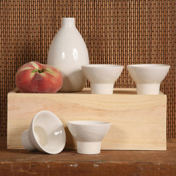 Nobu Sake Set - White - The traditional simplicity of the Nobu Sake Set in White makes this collection of a melon-shaped ceramic carafe and four flaring cups a pleasing nod to classic Japanese style.  Serve liquor ceremonially with the traditional vessels to create an evening to remember for your guests, or display amongst your drinkware for international flair that keeps up a clean, modish transitional look.