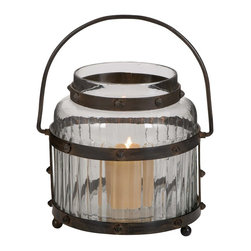 Glass Lantern with Metal Handle and The Frame Sport - Nothing beats the warmth and mellow glow of this Unique Metal Glass Lantern with Metal Handle and The Frame Sport! This traditional light source will add a rustic and old world charm to your home decor. The glass design on the case is made up of horizontal stripes that look great and ensure wide spread of light. The metal frame is bolted to the glass. Its small but strong metal legs prevent the glass from cracking if placed carelessly on an uneven surface. The stylish metal handle and the frame sport a tarnished and worn finish to complete the authentic antique feel of this glass lantern. The body of this lantern is made from high-quality, thick glass and is spacious enough to allow the easy placement of a candle. This elegant glass lantern is a perfect addition to tone down your home decor and add a touch of humble style to it. It comes with following dimensions: