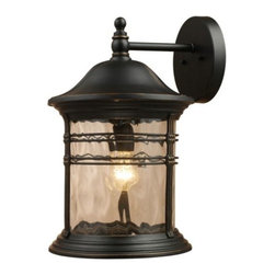 """ELK Lighting - Madison Outdoor Wall Sconce by ELK Lighting - Decorative water glass gives the ELK Lighting Madison Outdoor Wall Sconce a well-established look, handsome and classic. Inspired by early American design, the Madison Outdoor Wall Sconce incorporates the popular look of antique carriage lanterns, its strong frame featuring both thin and thick bands of Matte Black metal. Founded in Eastern Pennsylvania in 1983, ELK Lighting designs and delivers """"Lighting for Distinctive Homes."""" As such, the exclusive line of ELK Lighting products has extraordinary designer appeal matched by an emphasis on value and craftsmanship."""