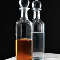 Column Decanter - Functional pieces with a sense of heritage, stately glassware elements like the Column Decanter add an air of tradition to your serving.  The ball stopper atop this slender cylindrical decanter makes this a classic solution for keeping liqueurs and vintages fresh, while its sleek, upright design makes it an ideal choice for creating a unified and space-saving look on your sideboard.