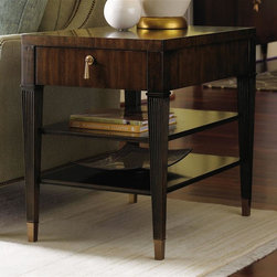 Lexington Furniture - St. Tropez Rochelle End Table - Hand painted gold stripping. One drawer. Two shelves. Brass ferrule. Hardware is custom designed in champagne gold finish. Drawer construction: English dovetails, wood runner and guides, drawer stop. Decorative metal in burnished gold. Warranty: One year limited. Made from quartered and cathedral walnut veneers on select hardwood solids. Rich walnut brown finish with medium luster. Minimal assembly required. 20.25 in. W x 28.25 in. D x 26 in. H (80 lbs.). Special Care Instructions from Lexington FurnitureSt. Tropez is an elegant interpretation of transitional design. While the collection has a couture appeal, the designs reflect an unpretentious feeling of luxury and comfort. The resort of St. Tropez is an international destination, with a marvelous blend of cultures, fashion and style. The roots are solidly traditional, but the vibe is chic and casual. The common thread, from a design point-of-view, is elegance without pretense. That is the essence of this collection glamour redefined. Where the beauty of traditional meets the sparkle of contemporary. St Tropez is an elegant interpretation of timeless transitional design. Shimmering silks and soft velvets take their cue from couture fashion. Every texture, every detail is purposely designed to distinctly surround and affirm the home in beauty and glamour.