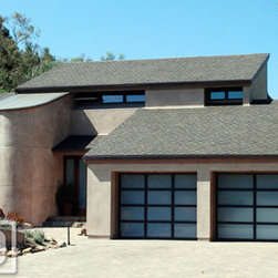 Orange County Modern Glass Garage Door in a Bronze Colored Frame & Frosted Glass - Orange County, CA - Modern style homes require garage doors that enhance the existing architectural elements typical of modern design. These full view style garage doors are a perfect complement to the curb appeal of this modern home's landscape and architectural style.