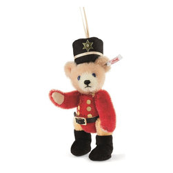 Steiff - Steiff Nutcracker Teddy Bear Christmas Ornament - Just like a real nutcracker, the little Teddy bear nutcracker is decked out festively for Christmas. He secretly hopes to meet his bear friend Emma and wants to look his very best for her. Just like her, he is an ornament - 12 cm, delicate and intricately fashioned of finest mohair. With bright colours, striking blue eyes, boots and leather belt, he is a sight to behold. He tops off the effect with a festive hat of black felt with a star sequin and six golden, hand-sewn buttons. And he looks every inch the part - even if he prefers leaving the actual business of cracking nuts to his wooden counterparts.