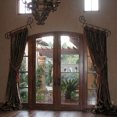 Draperies - Slant top stationary veranda panels with contrasting cuff and banding sewn into side hems, tied back and installed on custom wrought iron hardware.