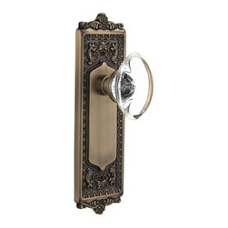 Nostalgic - Nostalgic Passage-Egg and Dart Plate-Oval Clear Crystal Knob-Antique Brass - With its distinctive repeating border detail, as well as floral crown and foot, the Egg & Dart Plate in antique brass resonates grand style and is the ideal choice for larger doors. Add our Oval Clear Crystal Knob, with its clean oval shape and smooth outward-curve, and you have the perfect accompaniment for Period, Rustic and Arts & Crafts style homes. All Nostalgic Warehouse knobs are mounted on a solid (not plated) forged brass base for durability and beauty.