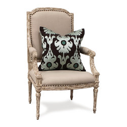 St. Germain Chair - Perfectly combining an inviting shape with formal detailing, fresh neutral colors with opulent carved outlines, the St. Germain Chair can be an elegant touch in rooms with any degree of texture or antique patina.  The armchair has a wooden frame with fluted legs, aster medallions, and a curved seat; carved acanthus leaves slope to padded arms.  This padding, like the other linen upholstery, is secured with Gothic Revival nailheads for craftsman depth.