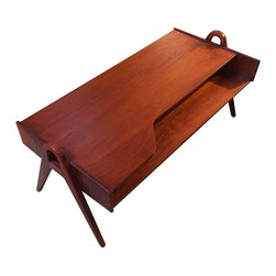 Used Berry Street Coffee Table - A classy teak coffee table with a Mid-Century twist. Made of warm-toned teak, it features sleek lines, slanted legs and and a shelf, creating a great place to stash magazines and television remotes.