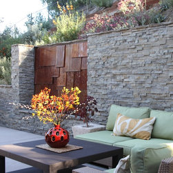 Ledger Stone Retaining Wall with Copper Waterfall - This copper waterfall adds beauty and delightful sounds enjoyed from both outdoor and indoor living rooms.  Photo by Orly Olivier.