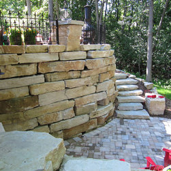 Patios - Patio with natural stone retaining wall and natural steps leading to lower patio.