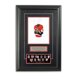 """Heritage Sports Art - Original art of the NHL 1998-99 Ottawa Senators jersey - This beautifully framed piece features an original piece of watercolor artwork glass-framed in an attractive two inch wide black resin frame with a double mat. The outer dimensions of the framed piece are approximately 17"""" wide x 24.5"""" high, although the exact size will vary according to the size of the original piece of art. At the core of the framed piece is the actual piece of original artwork as painted by the artist on textured 100% rag, water-marked watercolor paper. In many cases the original artwork has handwritten notes in pencil from the artist. Simply put, this is beautiful, one-of-a-kind artwork. The outer mat is a rich textured black acid-free mat with a decorative inset white v-groove, while the inner mat is a complimentary colored acid-free mat reflecting one of the team's primary colors. The image of this framed piece shows the mat color that we use (Red). Beneath the artwork is a silver plate with black text describing the original artwork. The text for this piece will read: This original, one-of-a-kind watercolor painting of the 1998-99 Ottawa Senators jersey is the original artwork that was used in the creation of this Ottawa Senators uniform evolution print and tens of thousands of other Ottawa Senators products that have been sold across North America. This original piece of art was painted by artist Nola McConnan for Maple Leaf Productions Ltd. Beneath the silver plate is a 3"""" x 9"""" reproduction of a well known, best-selling print that celebrates the history of the team. The print beautifully illustrates the chronological evolution of the team's uniform and shows you how the original art was used in the creation of this print. If you look closely, you will see that the print features the actual artwork being offered for sale. The piece is framed with an extremely high quality framing glass. We have used this glass style for many years with excellent results. We packag"""