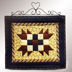 J & J Wire - J & J Wire Heart Quilt Rack - 769 - Shop for Caddies and Stands from Hayneedle.com! The J & J Wire Heart Quilt Rack may not be big enough to hold a full-size tapestry but it will proudly display your favorite miniature quilt heirloom block or needlework from any wall. Great for making your country kitchen seem even more charming this wall-mounted hanger has a sweet heart centered in a scrolled design. Made in the USA by skilled craftsman from sturdy iron with a durable black finish the hanger supports a solid wood bar with a medium stain. About J & J Wire Inc.Located at the Industrial Park in Beatrice Nebraska J & J Wire Inc. started 25 years ago as a wire-forming business manufacturing mostly houseware items. Since then the company has grown into a metal fabrication business serving customers in many different manufacturing sectors in the United States and Canada. From quilt racks to wine racks J & J Wire is committed to creating handmade works of art at affordable prices.