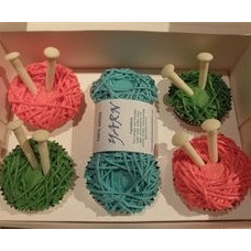 Adorable knitted cupcakes made of a cupcake and frosting with knitting needles i