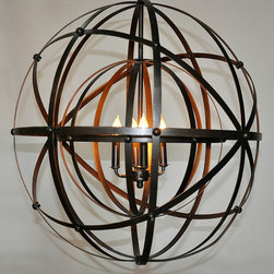 Alchemy Chandelier - Double spheres of metal bands offer visual movement and elaborate patterns of shadow in the Alchemy Chandelier. Each thin strip of natural metal is riveted to other curving staves for a flawlessly transitional presentation of a romantic, high-style ceiling light. Use with wall sconces for a sophisticated flood of multi-directional light or let it preside alone over an entryway to set a dramatic tone.