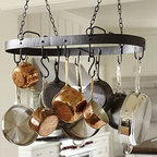 """Vintage Blacksmith Hanging Pot Rack - Our hanging pot rack frees up space in your cupboards and turns your pots and pans into an artful display. The broad band of wrought iron has a blackened finish and features rivet details. 33"""" wide x 17"""" deep x 7"""" high Made of iron with a blackened finish. Includes 10 hooks. Professional installation recommended. Catalog / Internet only."""