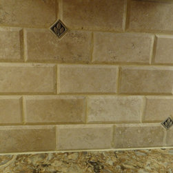 Downsizing does not mean less. - This is a natural beige tumbled and filled subway tile with tiny pewter inserts to break it up.  The pewter also ties in nicely with the handles on the cabinetry.  It is a beautiful completment for the Cambria Quartz countertops.