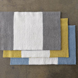 Stripe Bath Mat - The subtle stripes on these bath mats would be a good first step for anyone weary of this bold pattern. In an almost color block fashion, the simplicity of these rugs would be a pleasant addition to any bath.