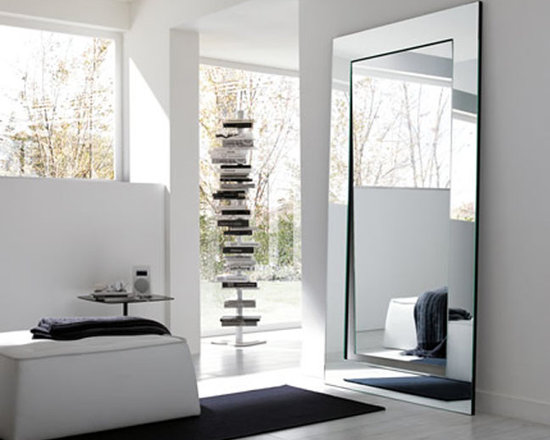 Gerundio Mirror - The large reflecting surface produces a three dimensional effect of the environment, that thus gains a greater depth. The surface and frame, slightly parted, split the reflecting image that, in a fine intellectual play, recovers itself only in the observer's mind. Available in floor or wall version.
