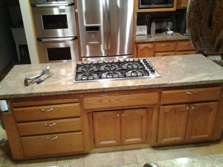 Replacing a drop in cooktop with a range top in a granite countertop.