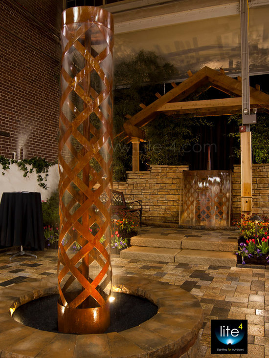Steel Fountains - This photo shows a fountain I created for the local flower and patio show in the spring of 2012.  The fountain is  approximately 10' tall and made of steel which has been woven into a loose basket weave pattern.  A smooth sheet of water spills over the top edge and slices its way down through the weave creating a very pleasant and soothing sound.  This feature was the centerpiece of the display.  There is also a large spillway falls in the back of the display that sheets water over the edge at a rate of 250 gallons a minute.  Besides designing and installing lighting, I design one of a kind custom fire and water creations as another avenue of my business.