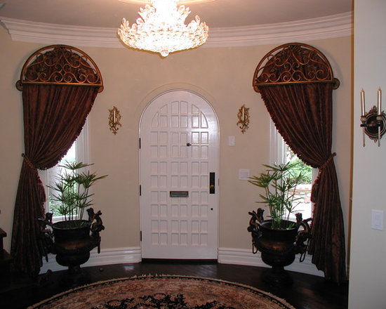 Cornice boxes - Arched top draperies fabricated to conform to the shape of the windows and door with custom made iron grill-work cornice to match and tied back with large tassel ties.