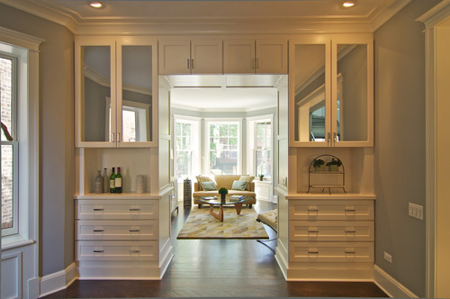 A door way with built-in cabinets around the walk way with mirrored cabinet doors.
