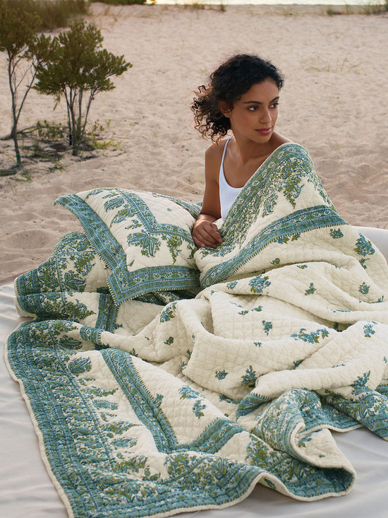Amadora Quilt - Intricate paisleys and posies are rendered in brilliant hues, conjuring the cerulean waters, tropical foliage and exotic beauty of a Balinese beach house. Relaxed and lighthearted as a summer day, this bright, cheerful quilt is sewn of soft-washed cotton cambric with lightweight cotton fill. Available in teal or azalea on ivory, it reverses to a tossed floral backing.