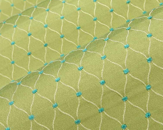 Placid Ogee Upholstery Fabric in Green - Placid Ogee Upholstery Fabric in Green has a thin white pattern woven across that is a cross between Ogee and Trellis. The light green base is punctuated by pops of bright blue. This contemporary fabric is perfect for upholstery projects or accent pillows. Made from a blend of 51% rayon and 49% polyester. This fabric passes CA 117 and UFAC II fire ratings. Cleaning Code: S; Width: 54″; Repeat: 7/8″ H 1 1/2″ V