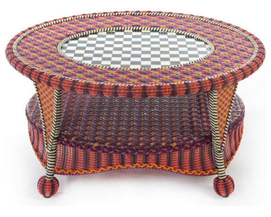 Sunset Outdoor Coffee Table | MacKenzie-Childs - Exotic yet familiar, the Sunset Outdoor Collection can instantly turn any terrace or porch into a luxurious retreat. Rich golds, oranges, purples, and blues, with flashes of magenta, recall blazing summer sunsets over Cayuga Lake. Hand-woven resin wicker is as durable and comfortable as it is striking. Cushions feature a printed pastiche of patterns, quintessentially MacKenzie-Childs: checks, squiggles and dots, scallops and leaves, and bold stripes.